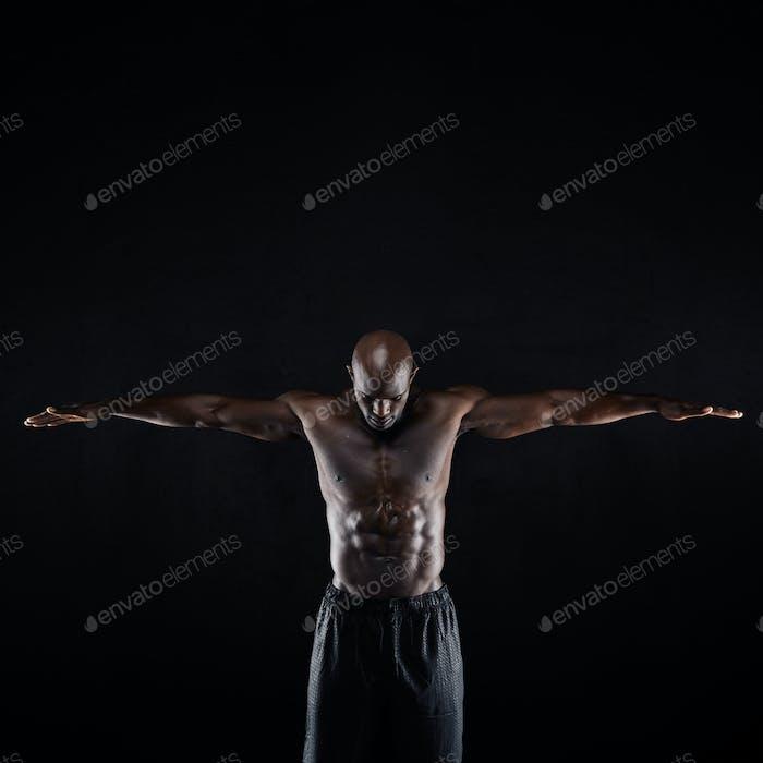 Fit junge muskulöse Mann streckt seine Arme