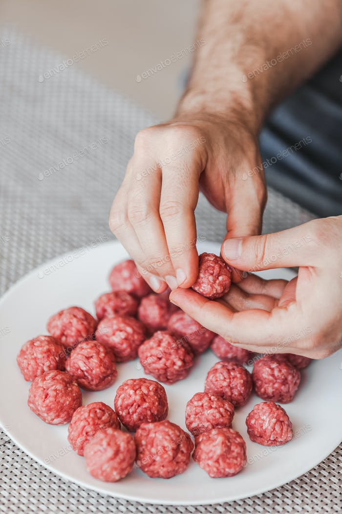 Man hands preparing meatballs with raw mincemeat