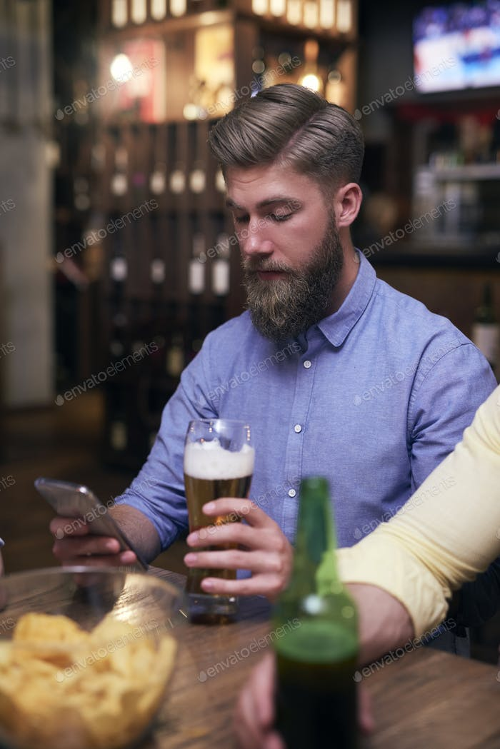 Hipster man using mobile phone and drinking beer