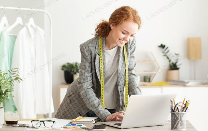Responding on business e-mail. Dressmaker working on laptop