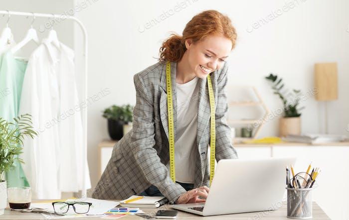 Responding on business e-mail. Dressmaker working on laptop