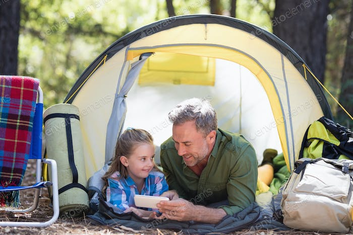 Father and daughter using mobile phone while relaxing in tent