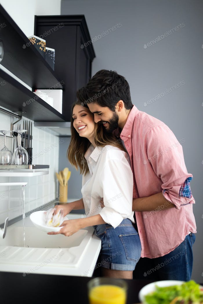 Young happy couple is washing dishes while doing cleaning at home