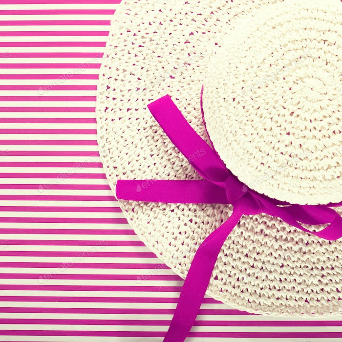 White straw sunhat on a striped magenta background
