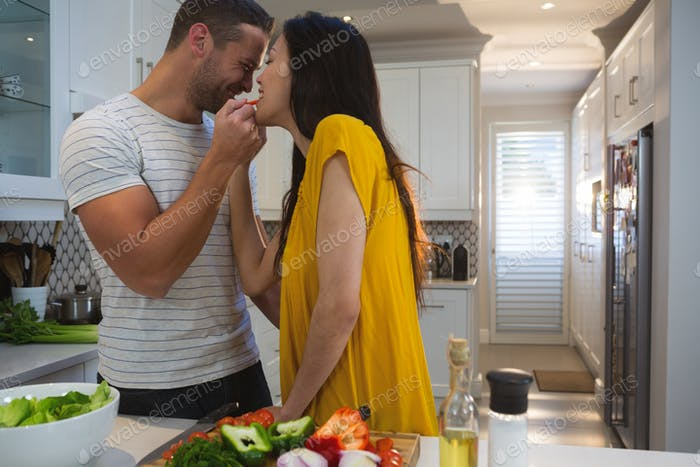 Man feeding woman in kitchen at home