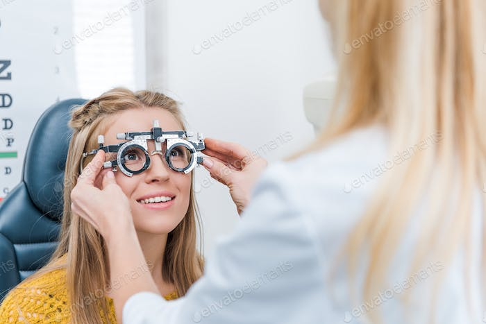 oculist and young patient with trial frame in clinic