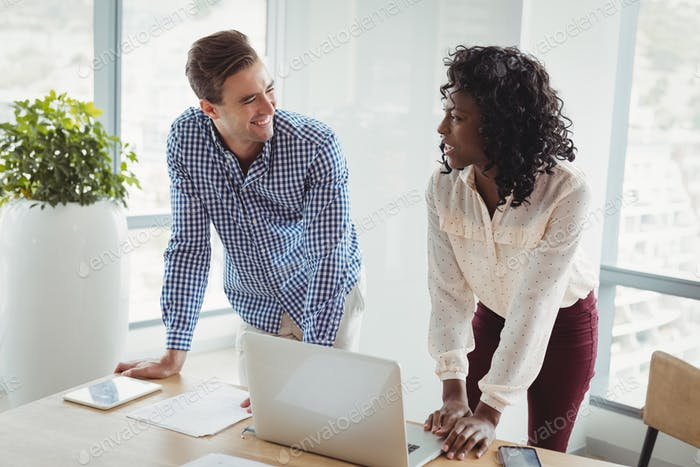 Smiling executives interacting with each other at desk