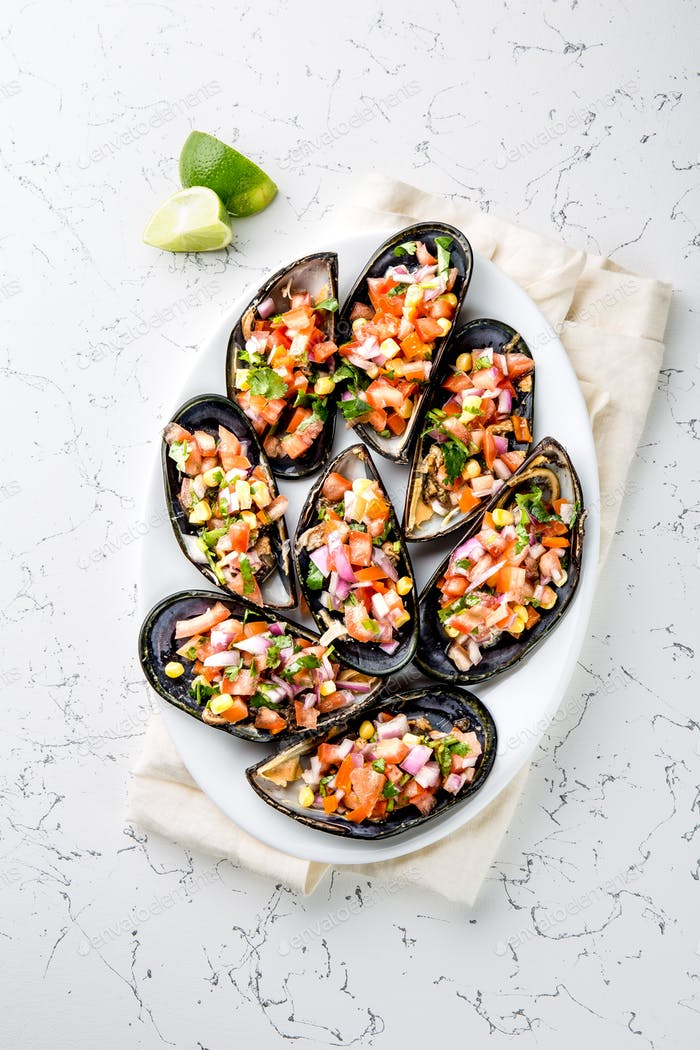Choros a la chalaca. Big mussels seasoned with purple onion, tomatoes, corn and lemon