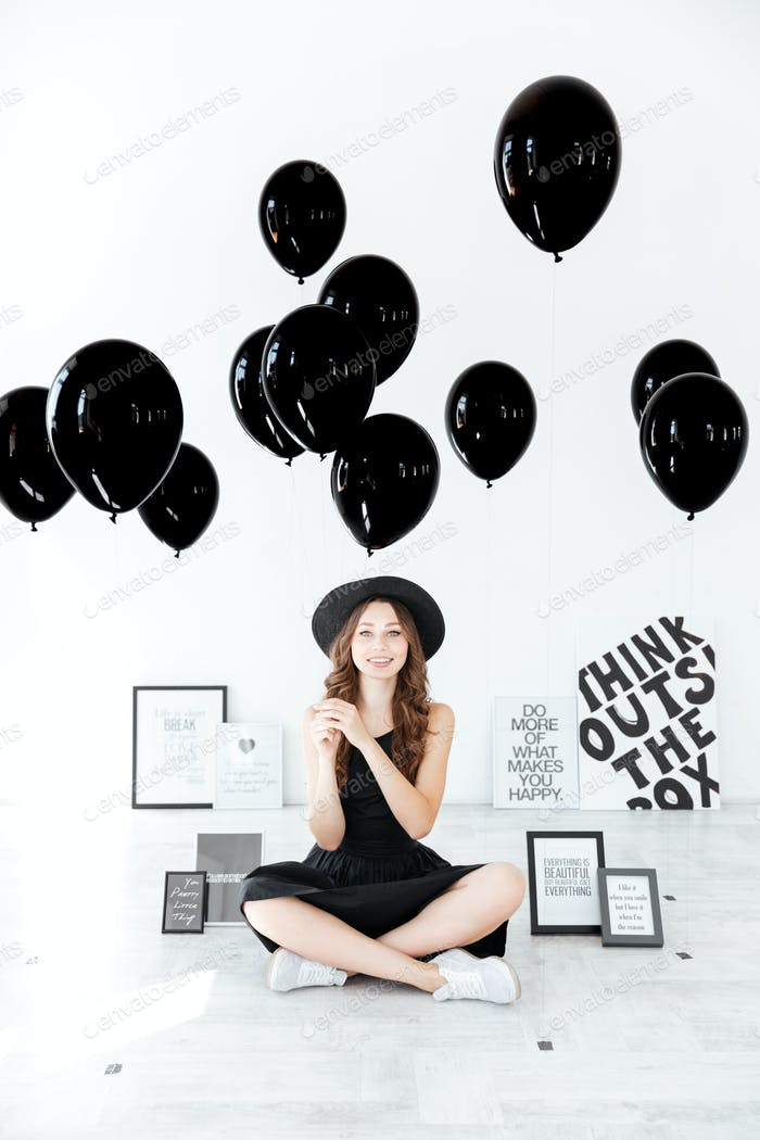 Happy woman sitting with legs crossed and holding black balloons
