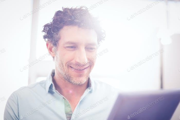 Happy casual businessman using tablet in his office