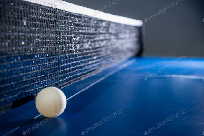 Closeup white table tennis ball and a black net