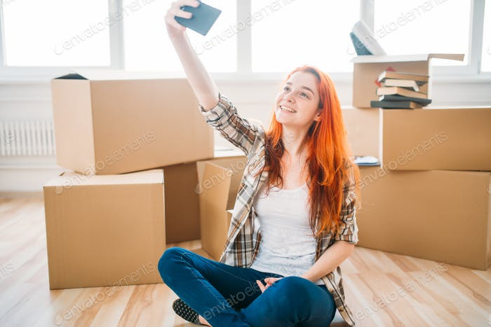 Woman among cardboard boxes makes selfie on camera