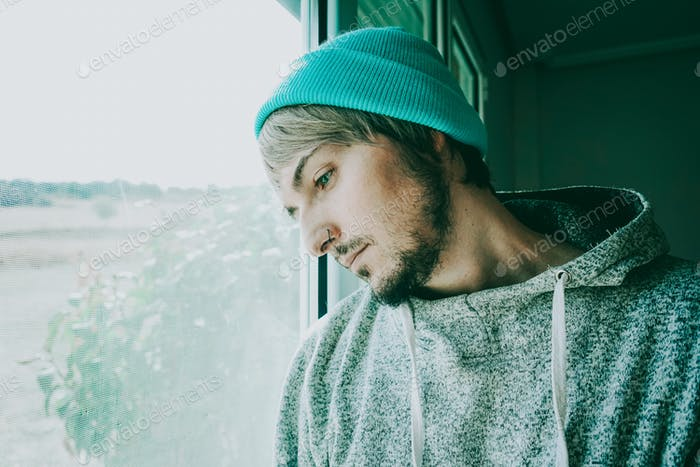 Young man alone in his home near a window
