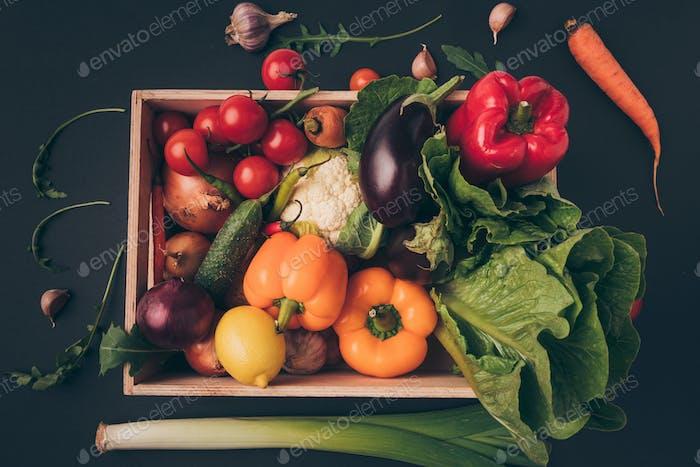 Draufsicht auf Holzkiste mit Gemüse auf grauem Tisch