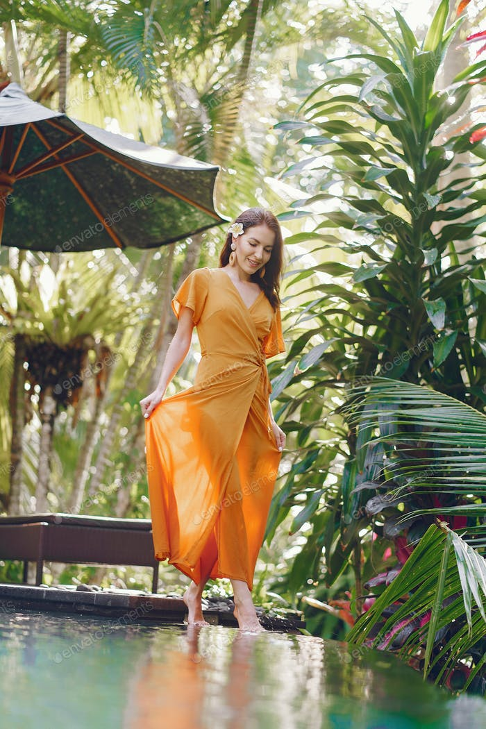 Woman in a yellow dress standing by the pool on a Bali
