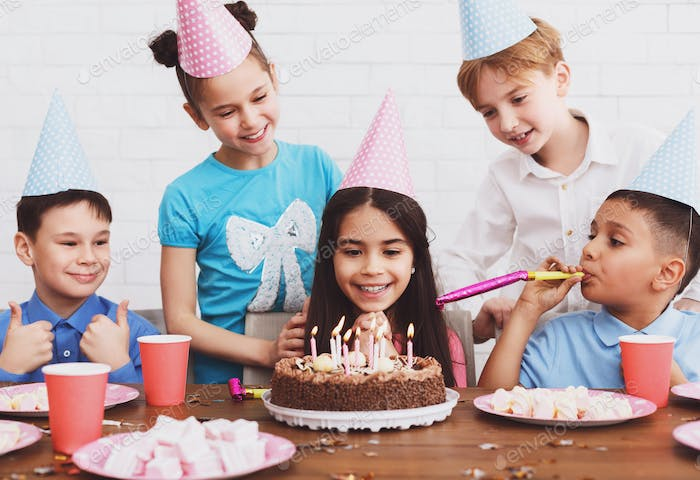 Birthday party. Girl making wish, looking at cake at home