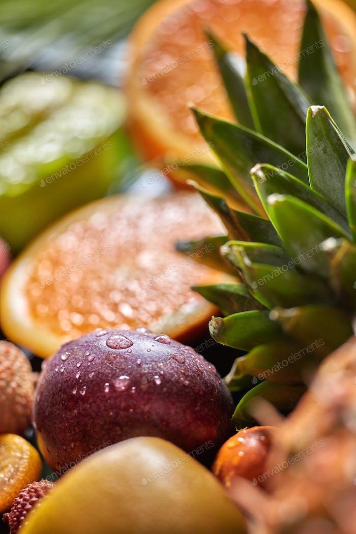 Tropischer frischer Hintergrund mit exotischen Passionsfrüchten in einem Tropfen Wasser und grüner Ananas