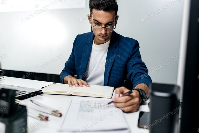 The architect dressed in a dark blue jacket works with documents on the desktop in the office