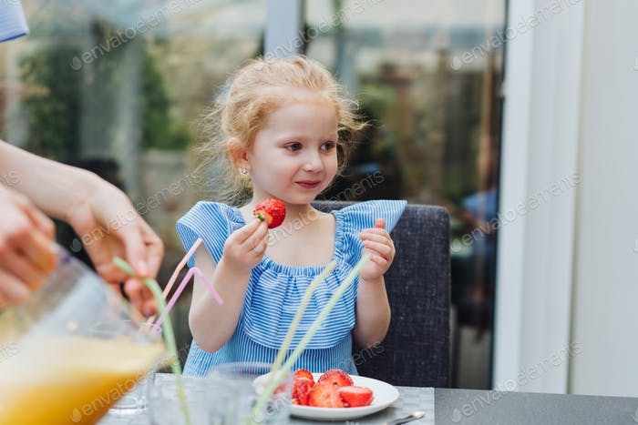 Little girl eating fresh strawberries