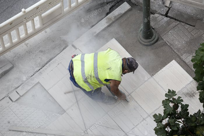 Bauarbeiter mit Winkelschleifer Reparatur eines Bürgersteigs