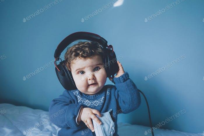 Pequeño bebé jugando con los auriculares de su papá