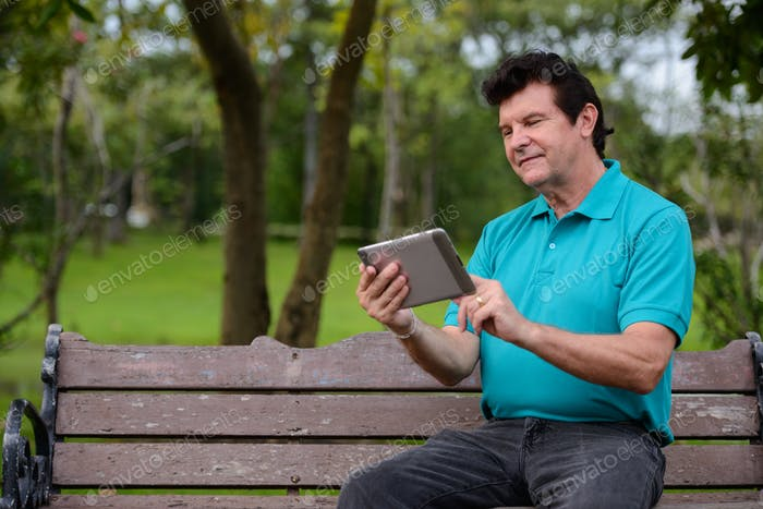 Portrait of mature handsome man relaxing at the park