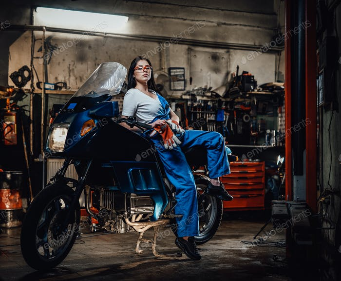 Hot brunette woman in blue overalls posing for a camera while leanign on sportbike