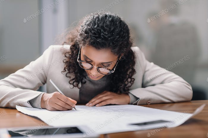 african american businesswoman doing paperwork in office