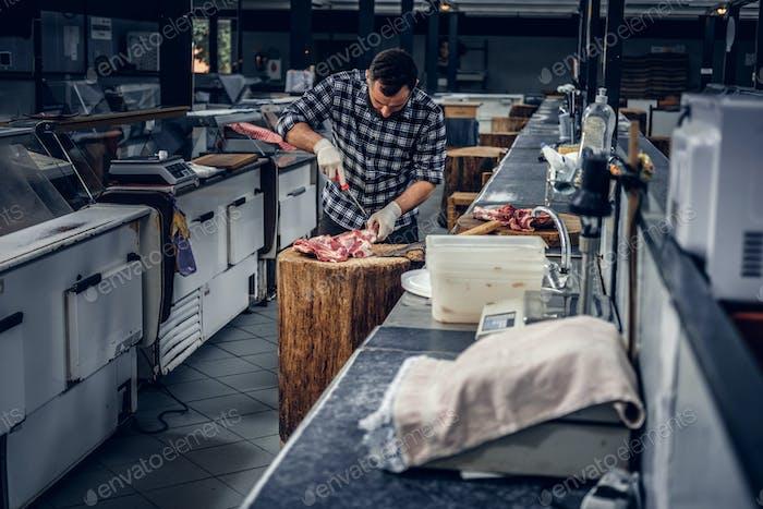 Bearded butcher cut fresh meat.