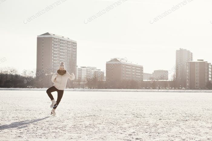 Woman skating on ice rink at park in city