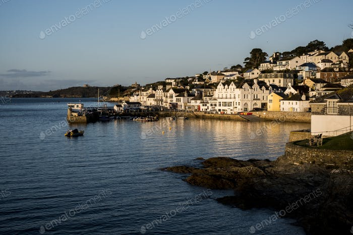 View along the seawall and facades of houses in Saint Mawes, Cornwall, UK.