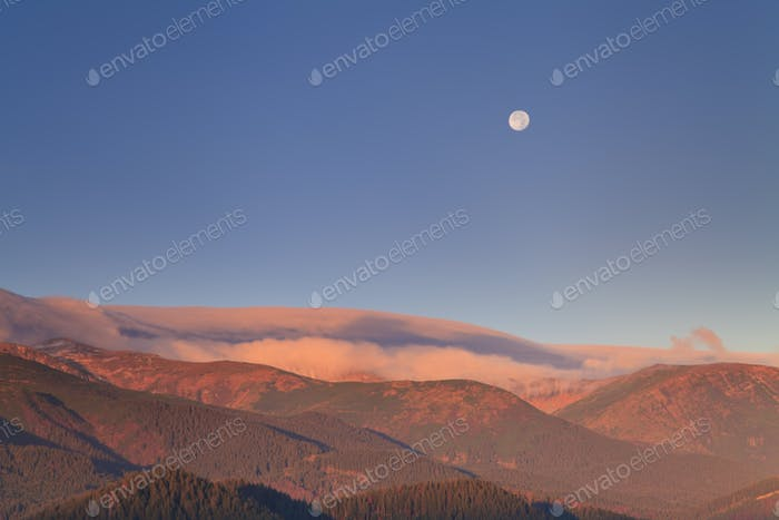 Moonrise in the mountains at dawn