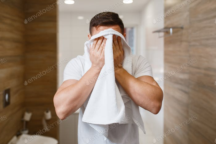 Man wipes his face with a towel, morning hygiene