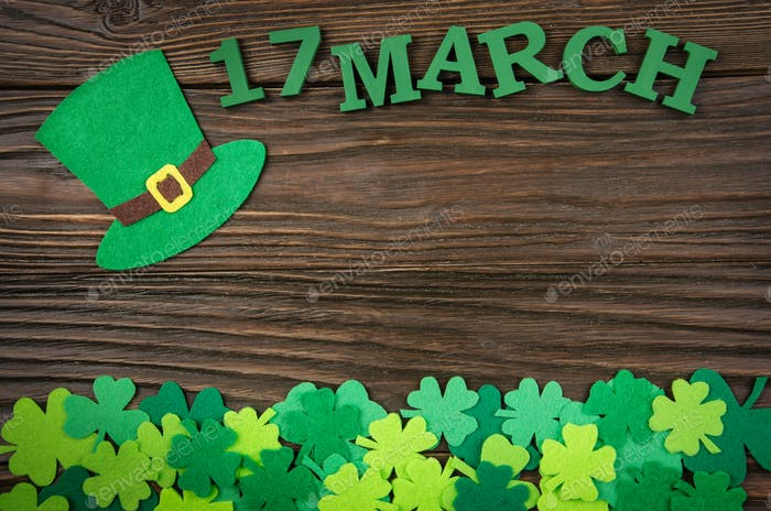 Happy Saint Patrick's mockup of handmade felt hat and shamrock clover leaves on wooden background.
