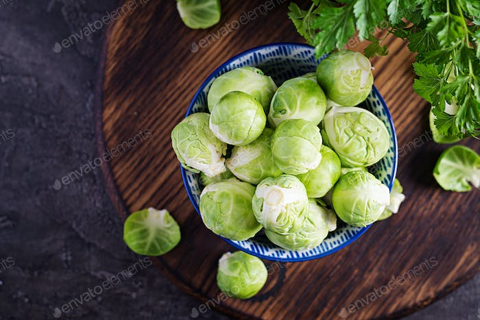 Fresh organic brussels sprouts in a bowl on a dark background. Healthy food.
