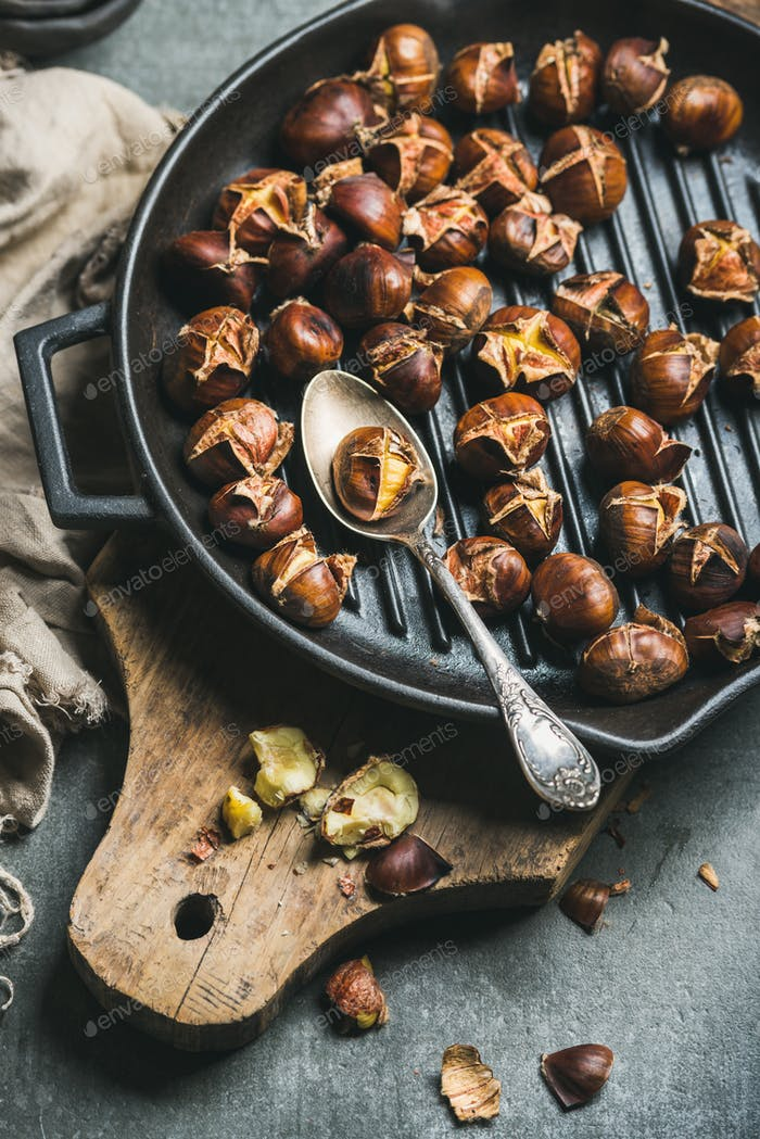 Roasted chestnuts in cast iron grilling pan over wooden board