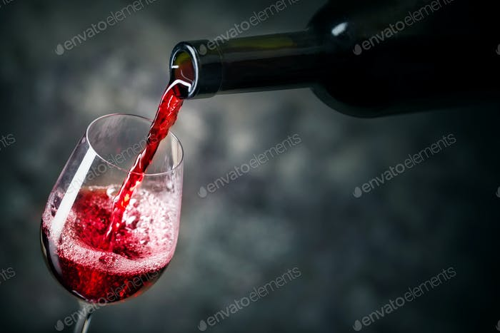 Red wine is being poured into glass