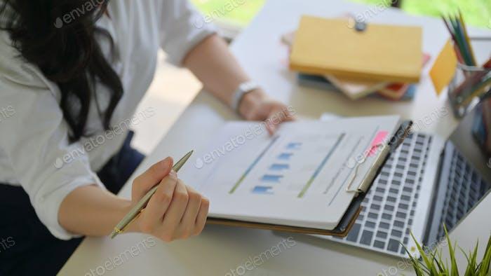 Ein Mädchen mit einem Stift und Datendiagrammen prüft Daten im Büro mit einem Laptop auf dem Schreibtisch.
