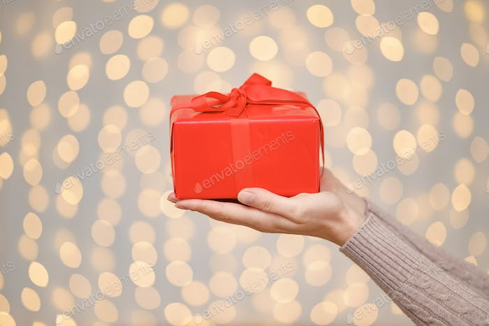 A magical glowing present box being holded by a woman hands