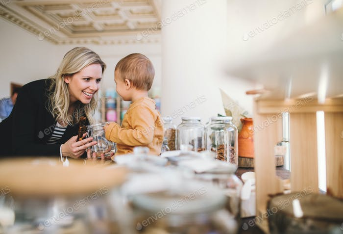 A young woman with a toddler boy buying groceries in zero waste shop.