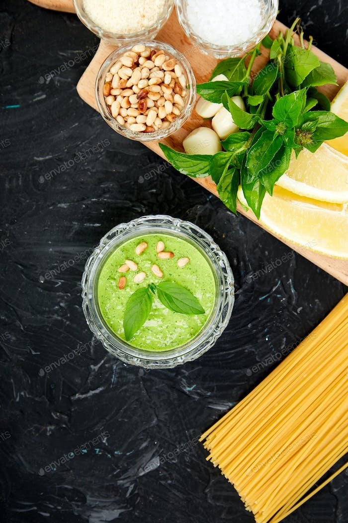 Homemade pesto sauce in glass jar with ingredients.