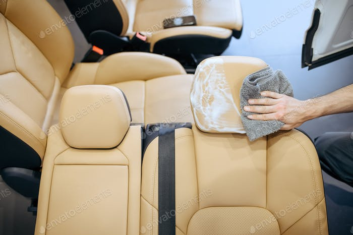 Worker with rag wipes removed car seat, detailing