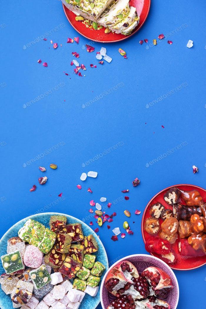 Nahöstliche Süßigkeiten auf blauem Hintergrund. Arabische Dessert, Baklava, Halva, rahat lokum, Sorbet, Nüsse