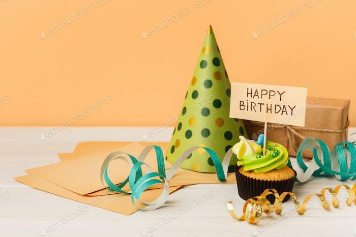 Köstliche Cupcake und Geschenk auf gelbem Hintergrund