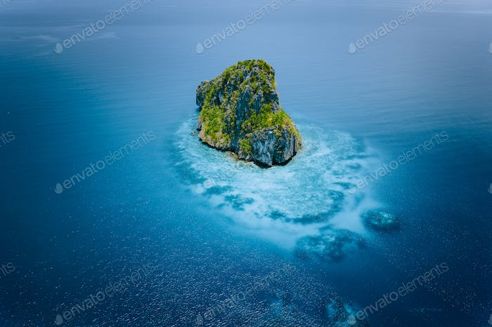Aerial drone view of a beautiful secluded cliff island surrounded by azure turquoise blue ocean
