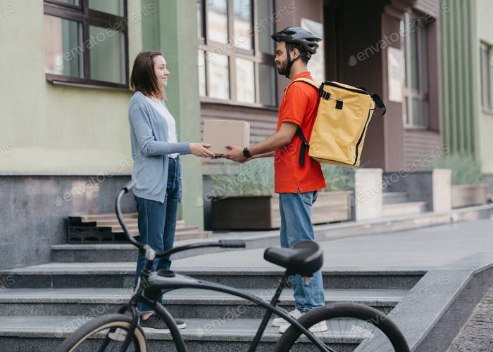 Courier services and online shopping. Young man with yellow backpack, helmet and bicycle gives girl