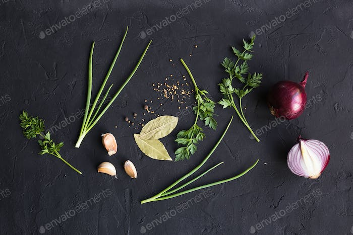 Garlic onion and parsley on a black background