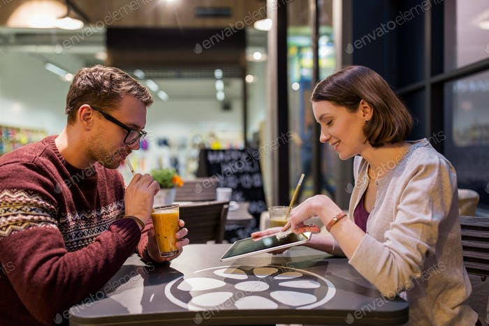 happy couple with tablet pc and smoothie at cafe