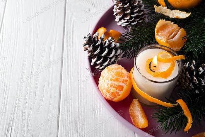 Christmas mandarines with lighted candle.