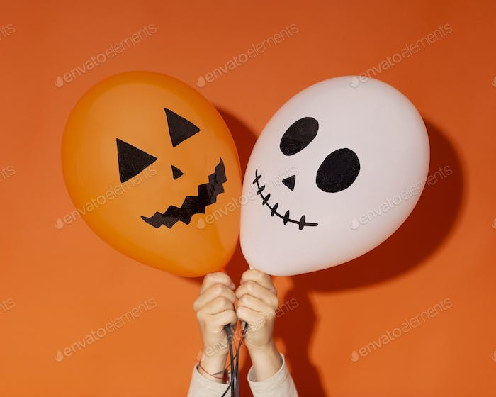 Halloween balloons with funny faces in woman hands